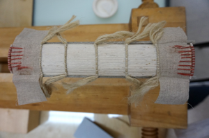 Figure 5: Spine of the text block after sewing, consolidation of the backfold of the quires, application of the endcaps with aerolinen linings and creation of new endbands.